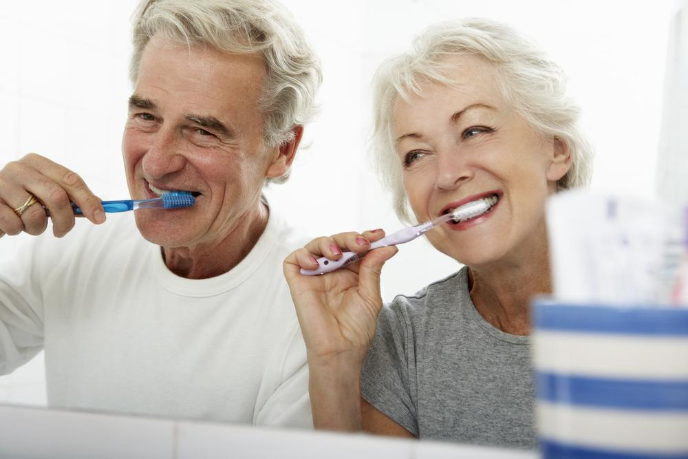 Older couple brushing their teeth together and smiling