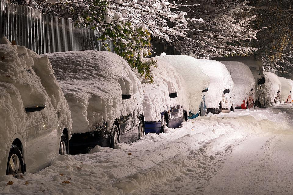 Snow covered cars on a street
