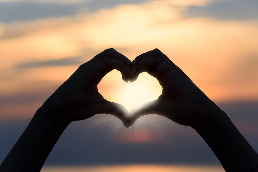 A heart shape made with 2 hands against a sunset