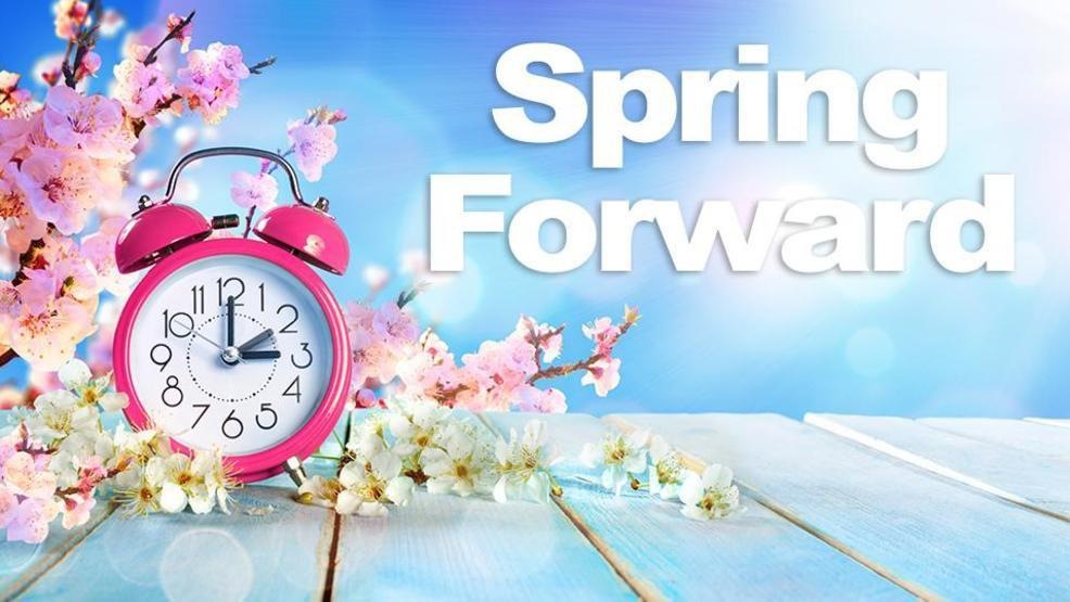 Pink and white flowers and a pink alarm clock on a wooden planked platform against a blue sky with the words Spring Forward