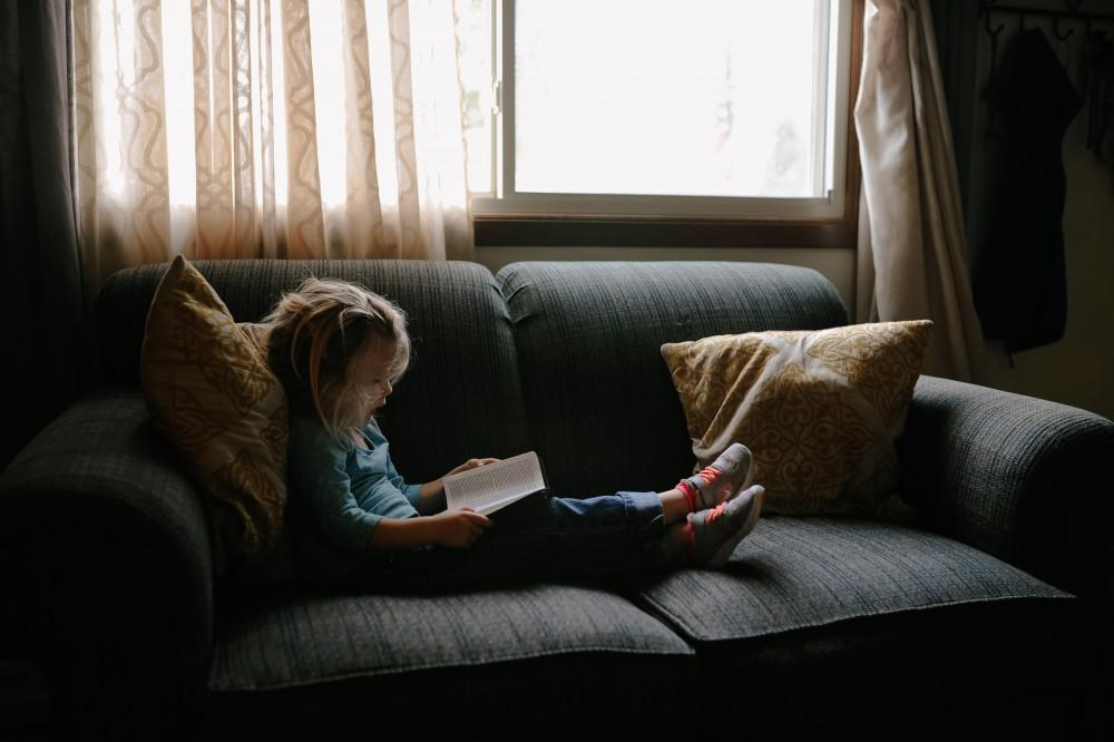Young child reading on couch