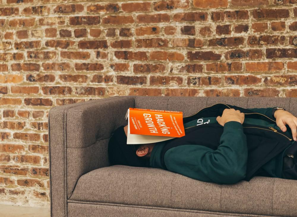 Man sleeping on a couch, open book on face