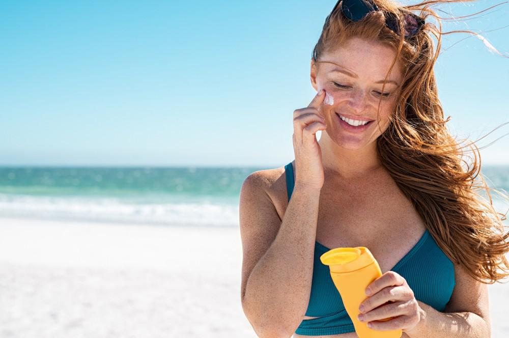 Woman applying sunscreen at beach