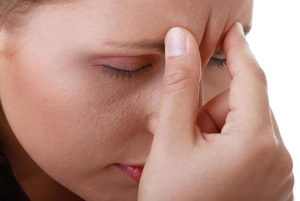 woman pinching forehead