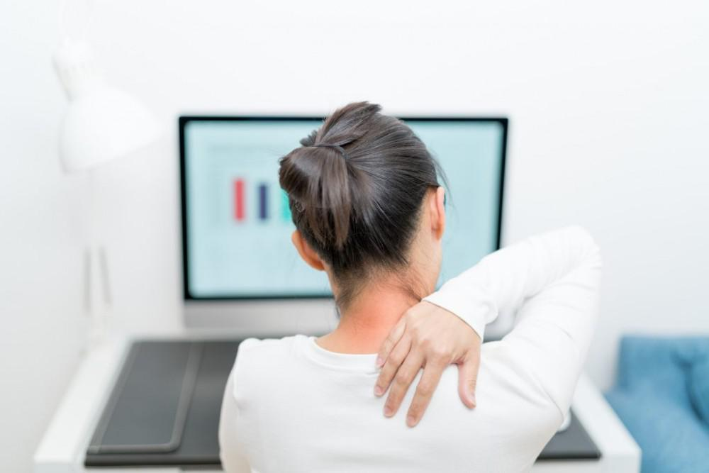 person grabbing their neck in pain