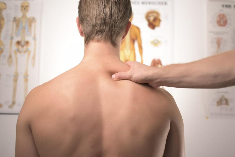 Hand gripping man's shoulder
