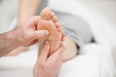 Podiatrist's hands examining patient's foot