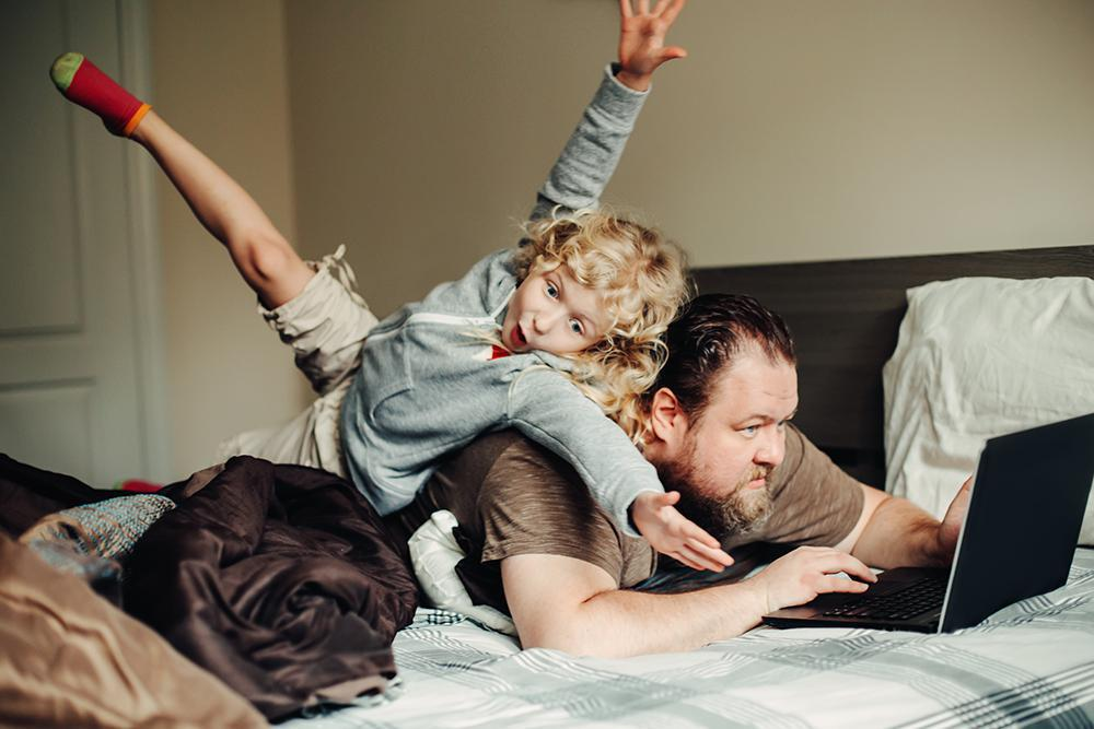 Father working from home with son jumping on back