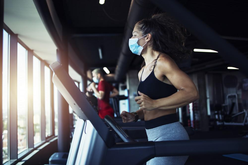 Woman running on treadmill with mask