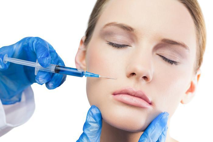 Woman getting botox injection on face