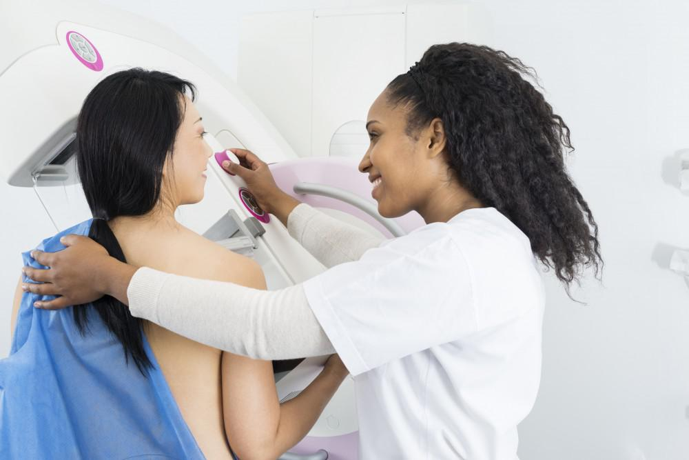 Woman getting mammogram with female technician