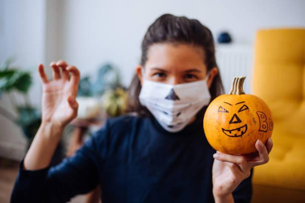 orthopedic patient wearing mask for halloween holding pumpkin