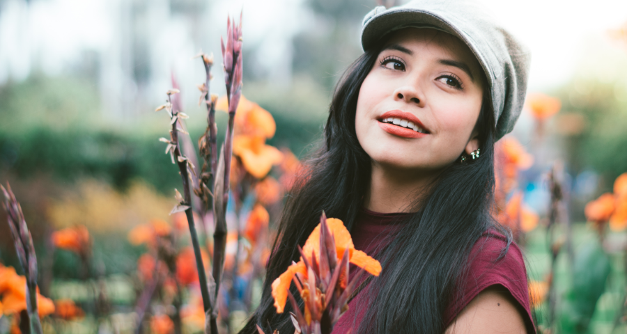 Young Latina woman wearing a hat surrounded by flowers with orange petals.