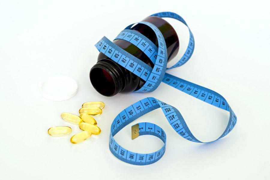A measuring tape wrapped around a bottle of weight loss medication with its cap off and yellow capsules spilled out