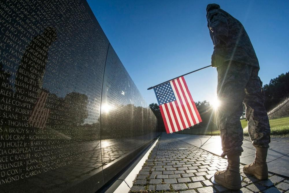 "A U.S. Army Reserve soldier reads some of the 58,307 names etched into ""The Wall"" of the Vietnam Veterans Memorial in Washing"