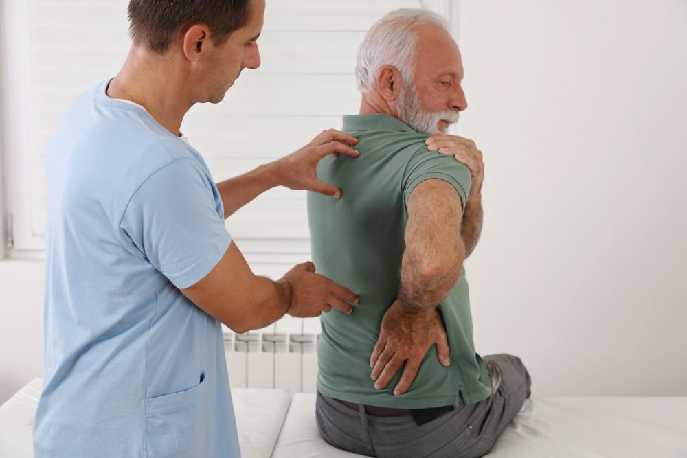 Doctor identifying pain points on patient's back. Patient holding shoulder and lower back.