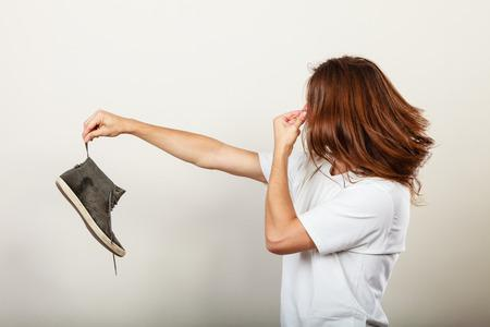 woman holding her nose, and a shoe at arm's length due to odor