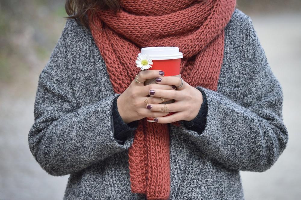 Woman holding a warm coffee