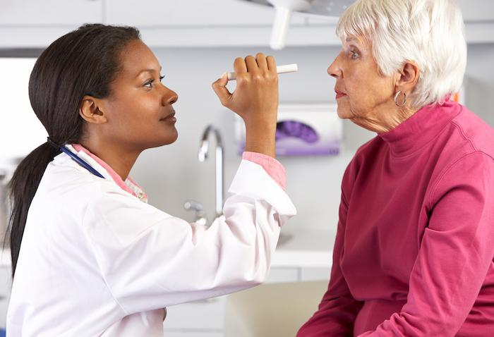 Doctor pointing light pen into patient's eyes