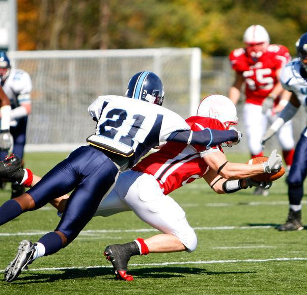 Image shows a football player getting tackled.