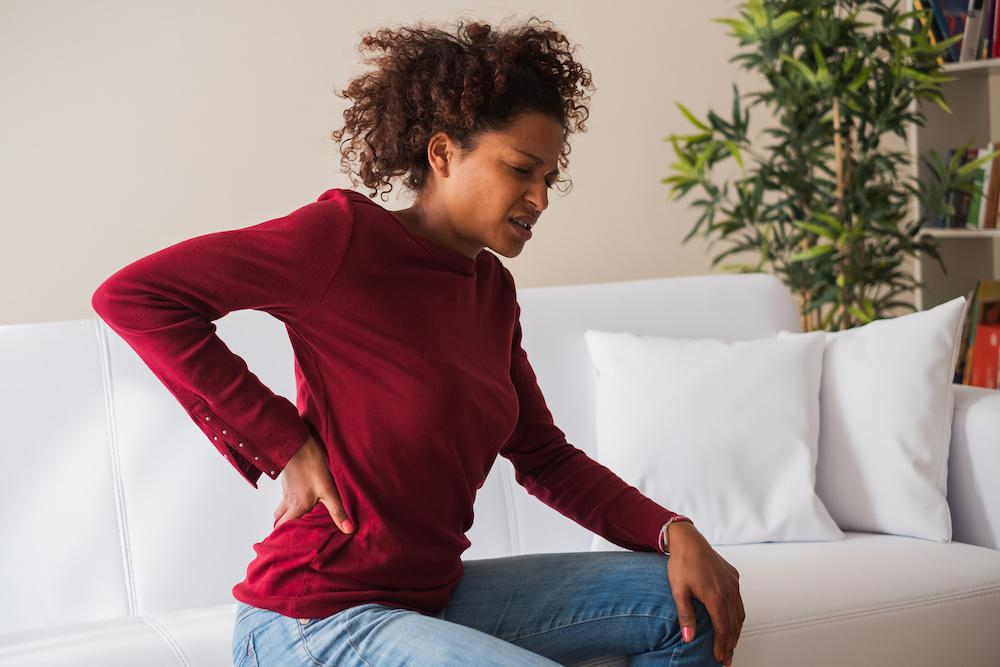 Brunette woman holding pain on her right lower back.