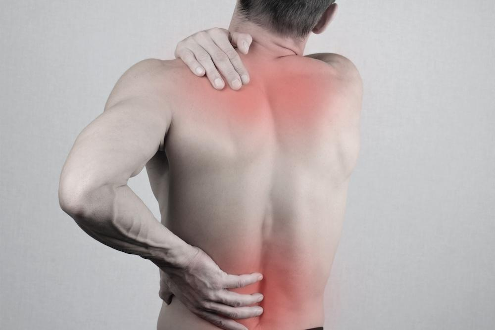 A man facing away with a hand reaching for his shoulder and lower back, highlighting red pain points on back.