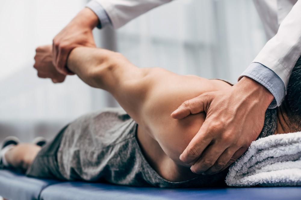 Chiropractor testing man's shoulder