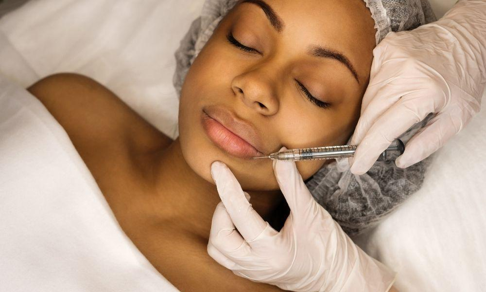 Black female receiving dermal filler injection