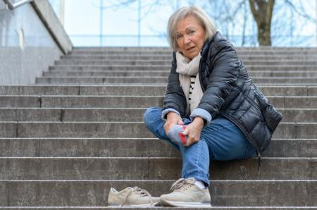 senior woman on stairs in winter with foot injury