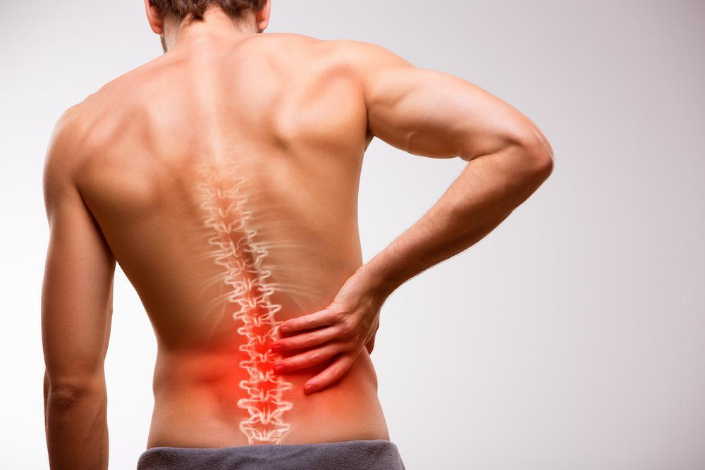 A man facing away with a hand reaching for his lower back, highlighting red pain points on back.
