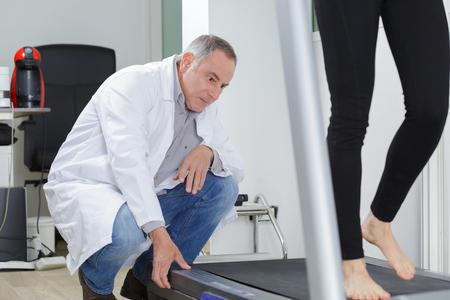 podiatrist looks at patient's gait and the way their foot strikes the surface of treadmill as they walk