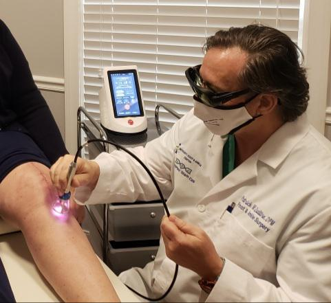 Dr. Qualtire applying laser therapy to a 3 week post-op incision.