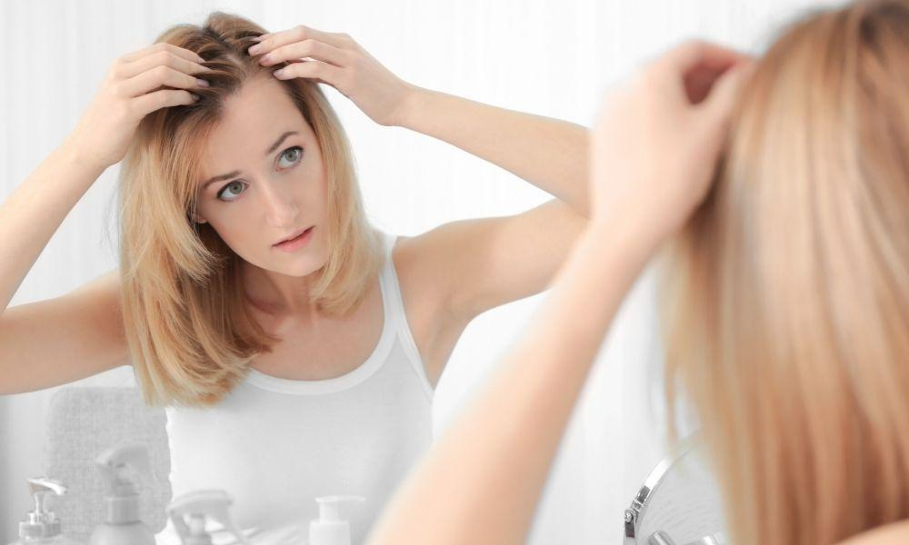 Caucasian female examining thinning hair in mirror