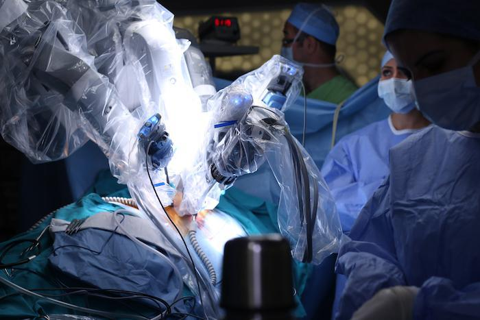 Robotic surgery with doctors in background