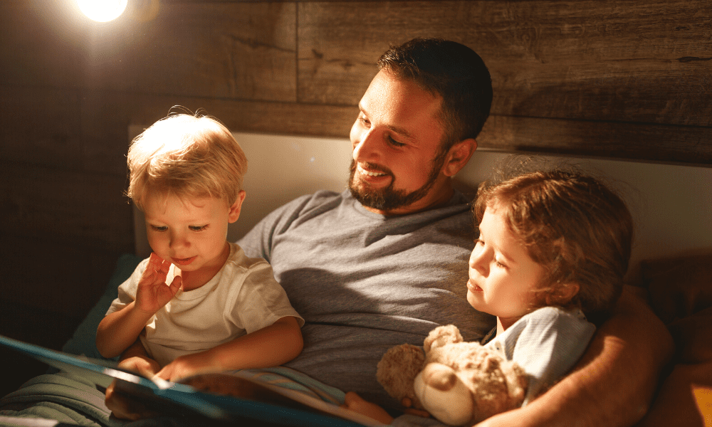 Father in Bed with Two children reading a bedtime story