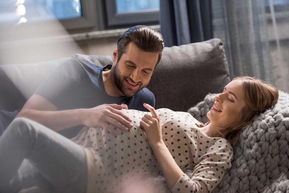 Man and pregnant woman laying down smiling at second trimester pregnancy belly.