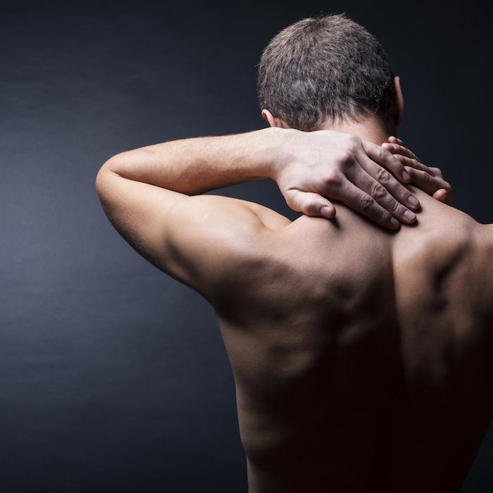 Back of man holding left hand on neck