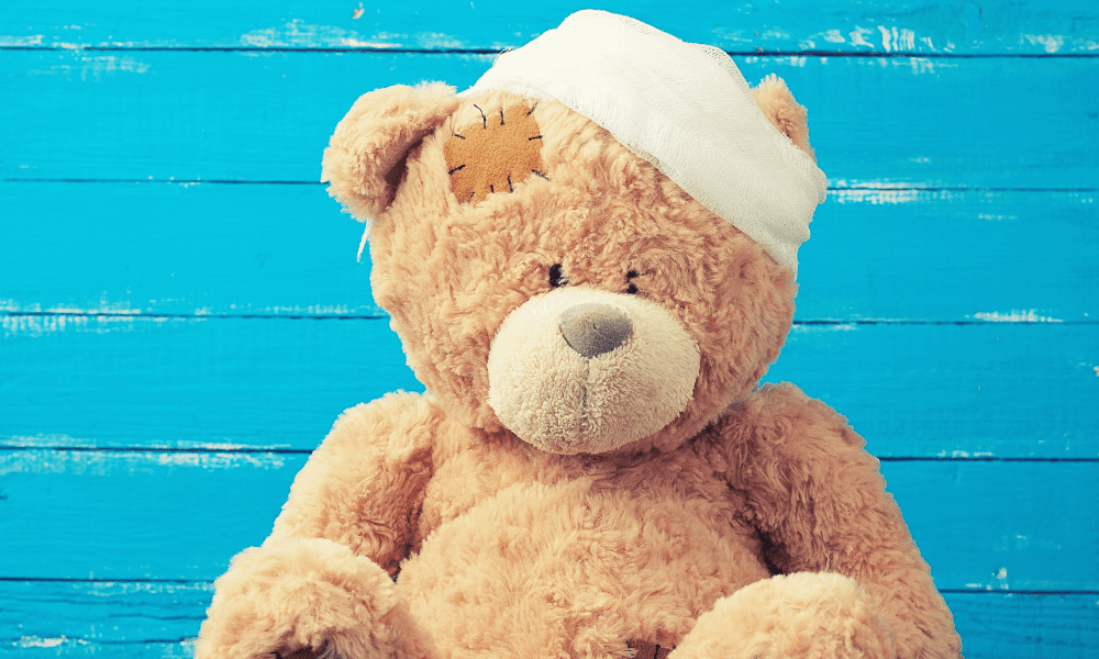 Teddy Bear with bandage on head and blue wall behind him