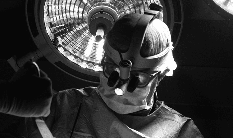 Black and white photo of spine specialist, Colin Crosby, MD, performing surgery