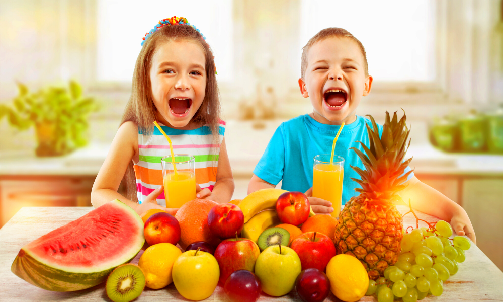 2 kids sitting at a table with a pile of various fruits in front of them