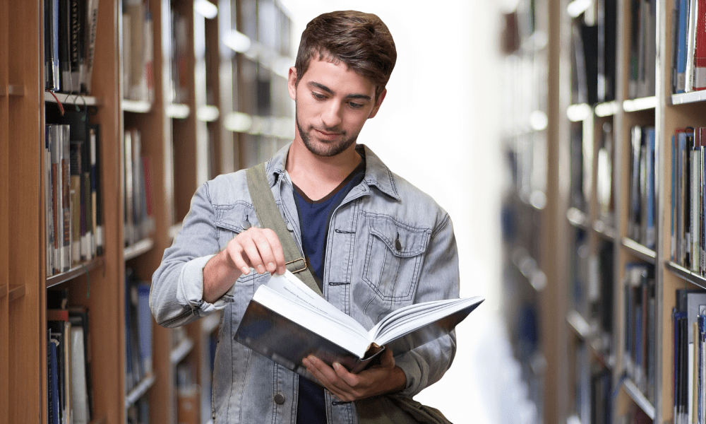 College student in Library holding a book and studying