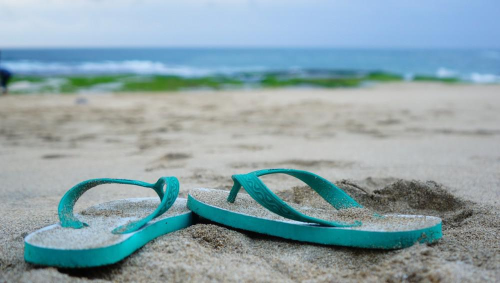 Teal flip flops dusted with sand on a beach with greenery and the ocean in the background.
