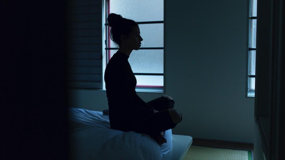 Woman sitting alone in the dark