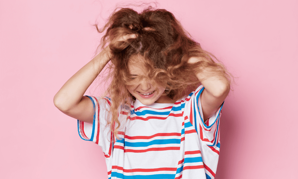 young girl in stripped shirt pulling her hair in frustration
