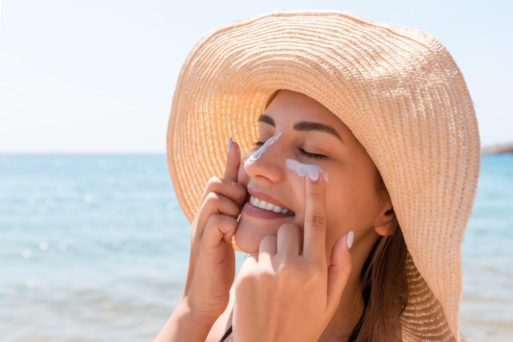 Smiling woman applying sunscreen to both cheeks while wearing a sun hat. The ocean glistens in the mid-day sun in the backgro