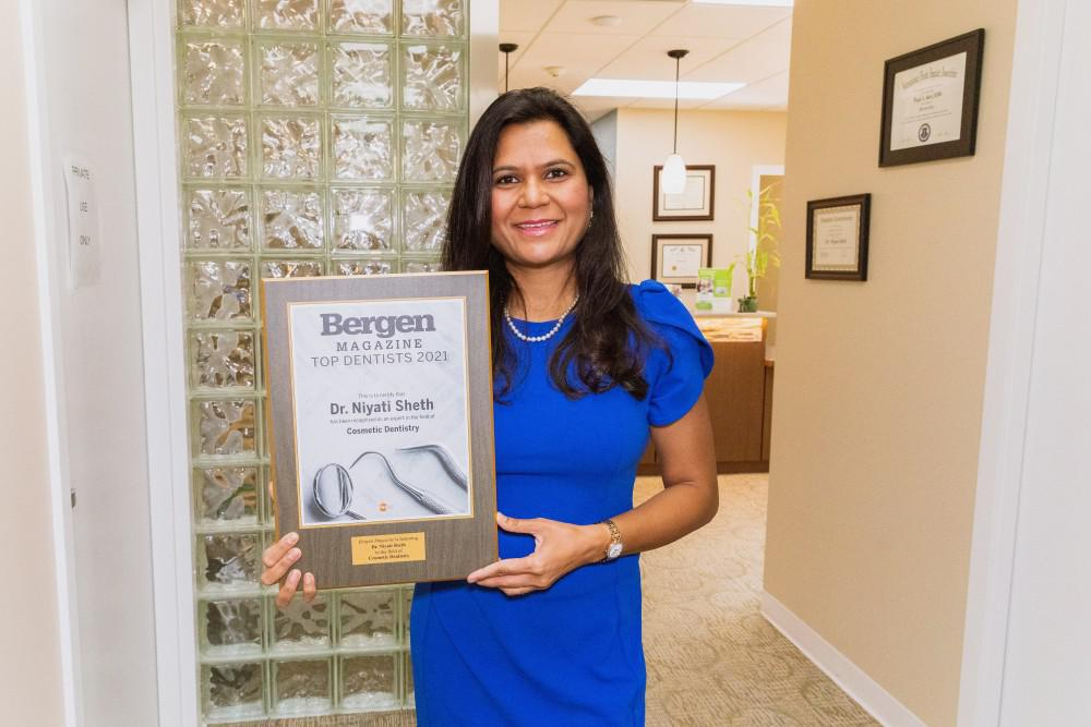 Dr. Sheth with the top dentist plaque