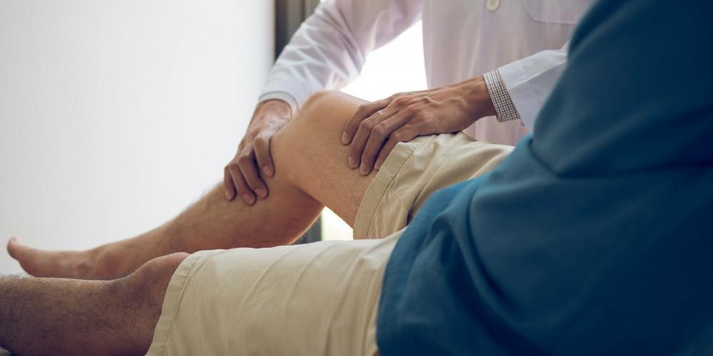 Doctor holding patient's knee