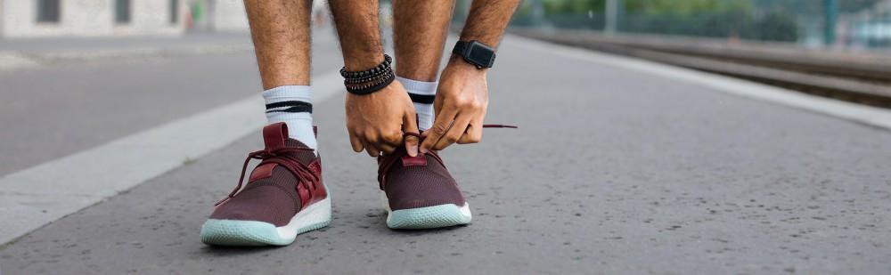 Man on a run tying shoe