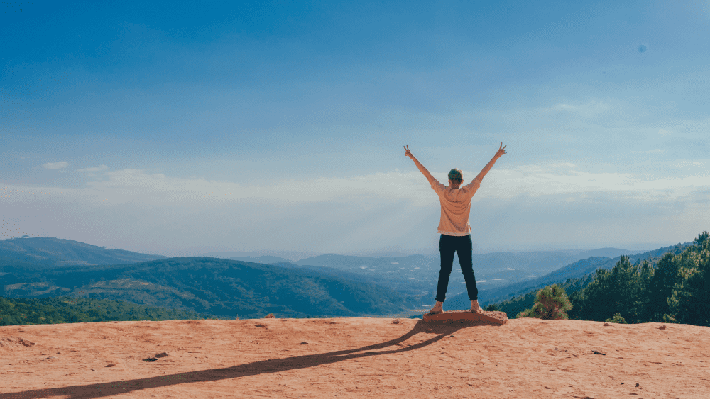 Woman with arms in the air looking over valley