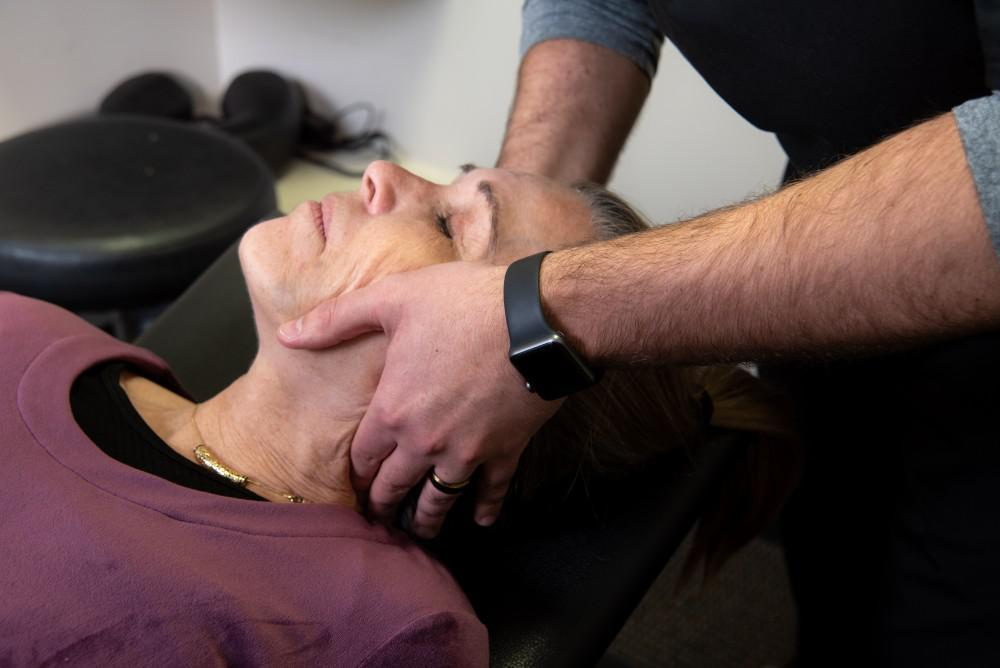 male chiropractor adjusting a female's neck on a chiropractic table